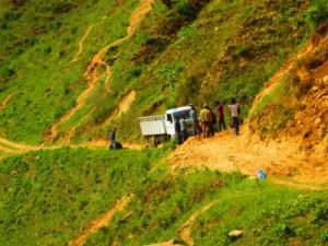 山間の険しい道をトラックにて物資を運ぶ